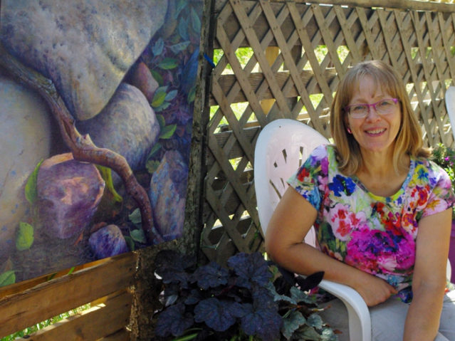 Judy sitting in her garden beside a painting of rocks