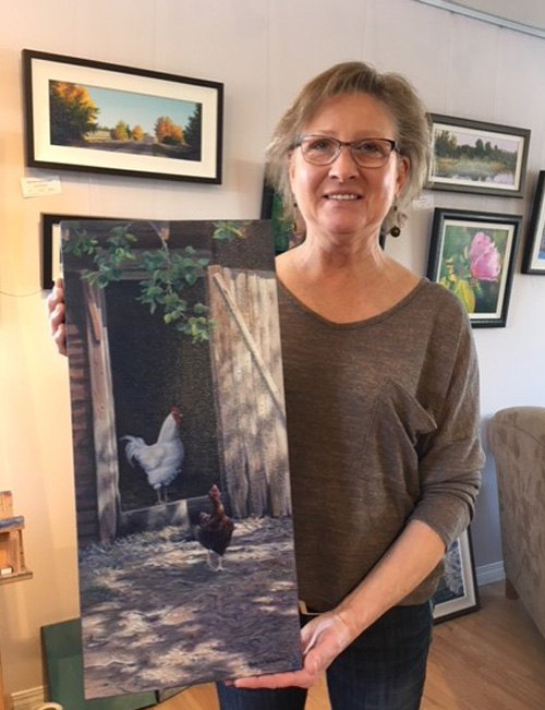 a woman holding a painting of two chickens