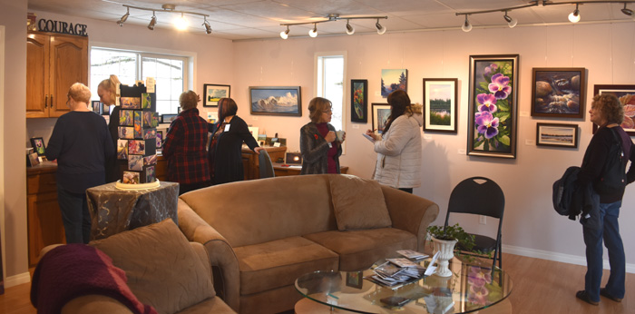 room filled with people and artwork on the walls