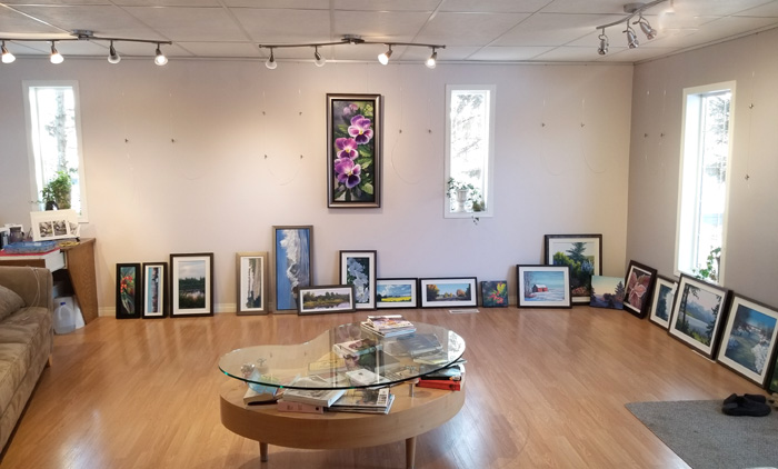 putting on a show, large room with paintings placed on the floor around the perimeter