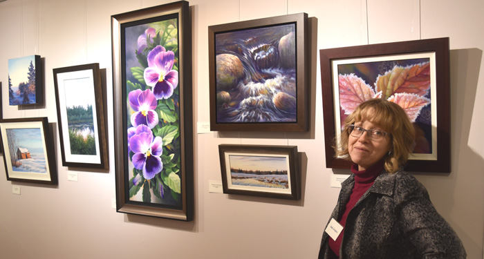 a woman standing beside several paintings hanging on the wall